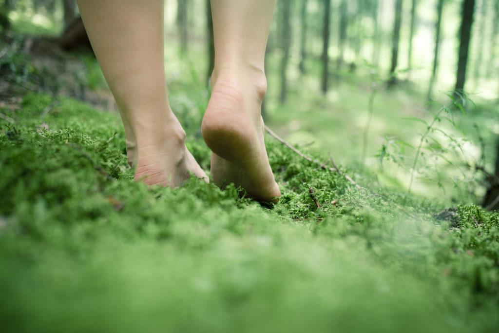femme qui marche pieds nus dans la forêt